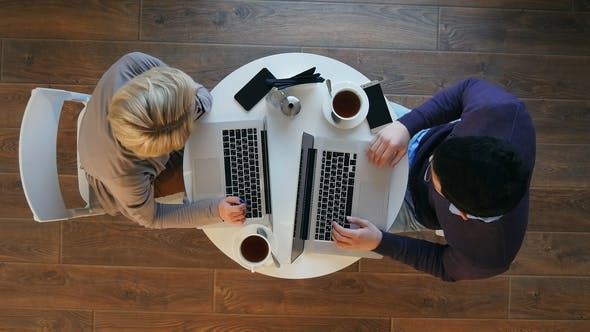 Thumbnail for Young Successful Business Couple Is Discussing Documents, Drinking Coffee and Smiling While Working