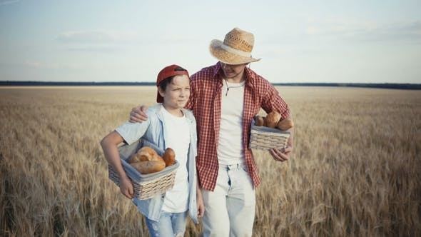 Thumbnail for Young Farmers Are Walking Along the Wheat Field with Bread Baskets
