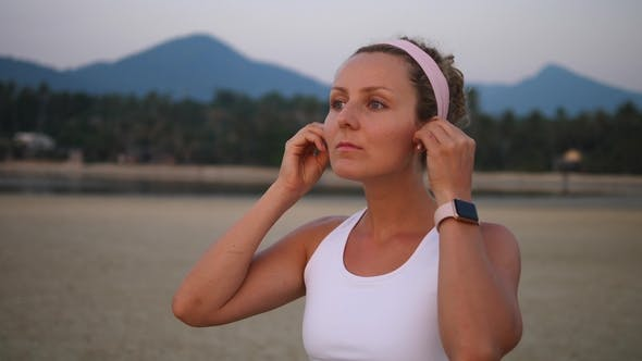 Thumbnail for Young Woman Wearing Smartwatch And Wireless Earphones Doing Sports On Beach