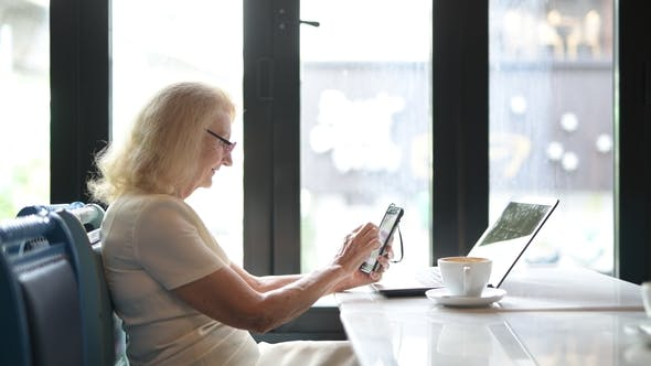 Thumbnail for Happy Senior Elderly Woman Using Mobile Phone And Laptop