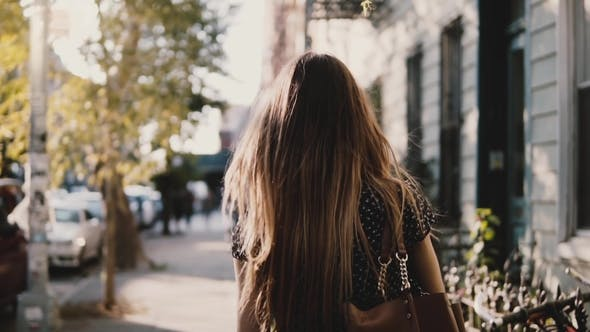 Thumbnail for Back View Happy Caucasian Girl with Flying Hair Walking Along Sunny City Street, Living Casual