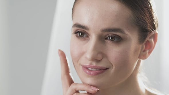 Healthy Face Skin. Beautiful Woman Touching Beauty Face