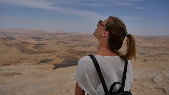 Thumbnail for Young Woman with Backpack Standing on Cliff's Edge Looking at Sky and Turning Around