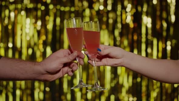 Thumbnail for Deux mains avec verres de vin de champagne ou cocktail pour faire du pain grillé sur fond doré