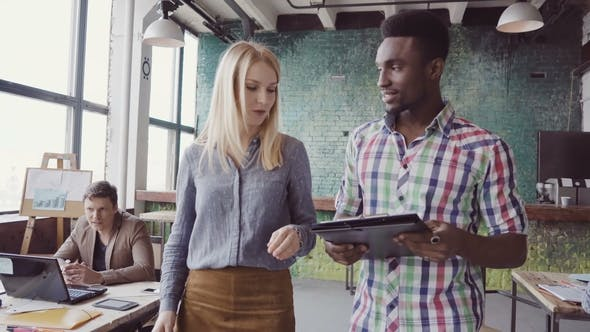 Thumbnail for Two Colleagues Walking Through the Modern Office and Talking. African Man and Caucasian Woman