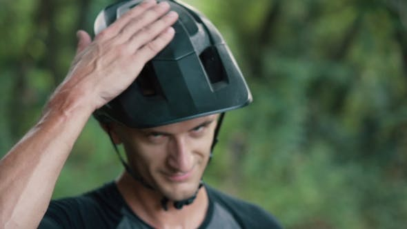 Thumbnail for Man Cyclist Knocks His Hand on Helmet on His Head