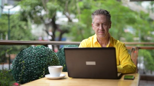 Thumbnail for Mature Man Sitting In Coffee Shop While Using Laptop Computer And Mobile Phone