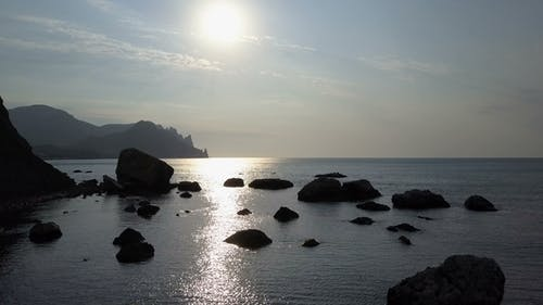 Flying Backward Over the Sea Surface with Rocks and Stones at Sunrise. Mountains, Rocks, Stones in