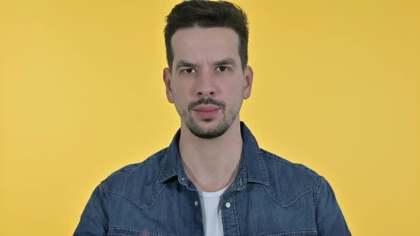 Thumbnail for Portrait of Attractive Young Man Saying No By Finger, Yellow Background