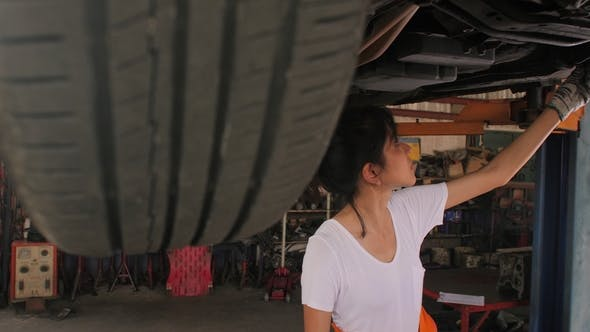 Thumbnail for Young Beautiful Car Mechanic Inspects the Car Undercarriage Way in Garage.