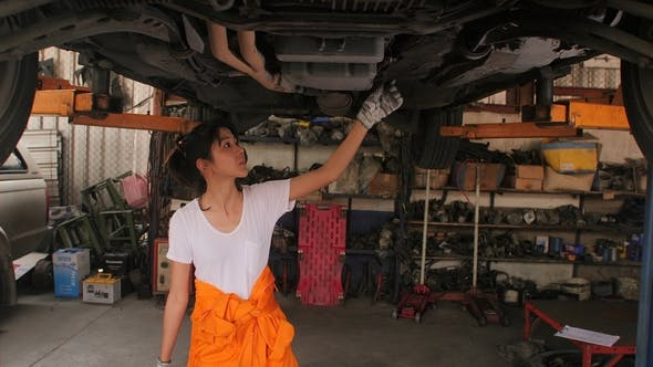 Thumbnail for Young Beautiful Car Mechanic Inspects the Car Undercarriage Way in Garage