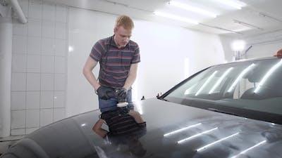 Man Sedulously Polishing Bumper of Car