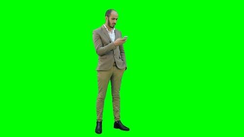 Businessman Using Mobile Phone on a Green Screen, Chroma Key