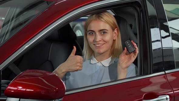 Cover Image for Happy Female Driver Showing Her Car Keys and Thumbs Up