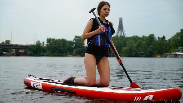 Beautiful Young Girl Swims on a Kayak