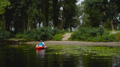 Young Guy Is Lying on a Kayak Near the Shore