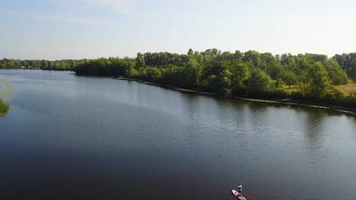 Three Young People Are Kayaking on the River