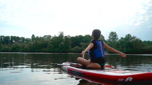 Young Girl Practice Yoga on Kayak