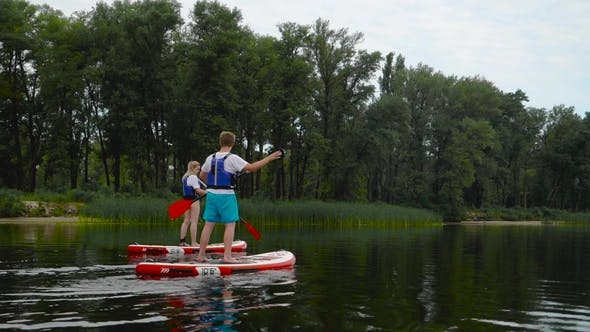 Couple Is Floating on Kayaks Along the River