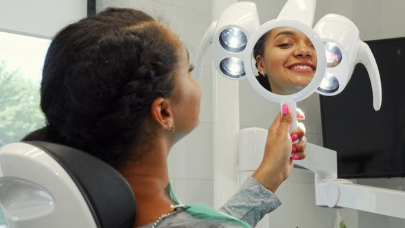 Thumbnail for Cheerful African Woman Smiling Examining Her Healthy Smile in the Mirror