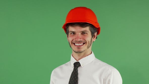 Thumbnail for Cheerful Male Engineer Smiling Putting on His Hardhat