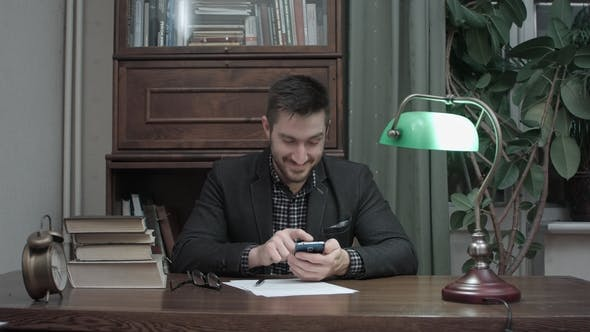 Thumbnail for Young Writer at His Desk Happily Messaging on Mobile Phone