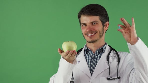 Thumbnail for Cheerful Male Doctor Holding Vitamin Pill and an Apple