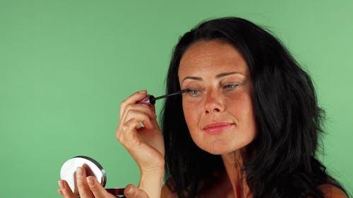 Beautiful Mature Woman Applying Makeup on Green Chromakey