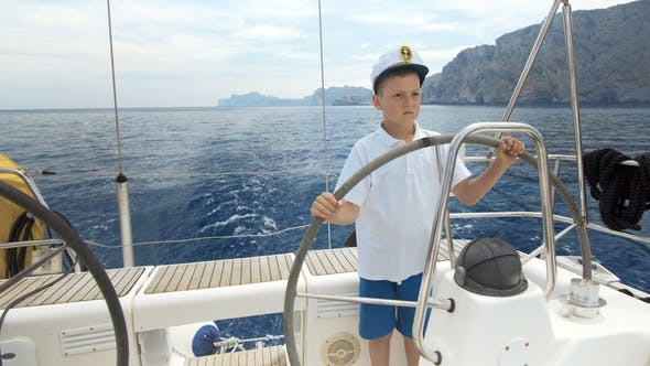 Thumbnail for Litle Children Captain at the Helm Controls of a Sailing Yacht During Race