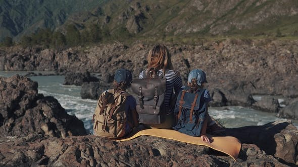 Thumbnail for a Young Traveler Mum Sits on the Edge of a Cliff Near a Mountain River with Her Children. Family of
