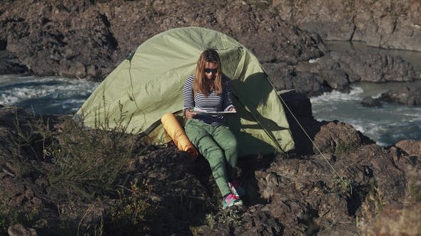 Thumbnail for Girl Is Studying a Map Sitting By the Tent on the Edge of a Cliff Near a Mountain River
