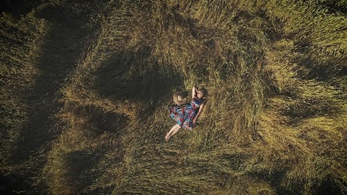 Aerial. a Young Woman in a Bright Dress Lying in the Hayloft. The Concept of Unity with Nature and