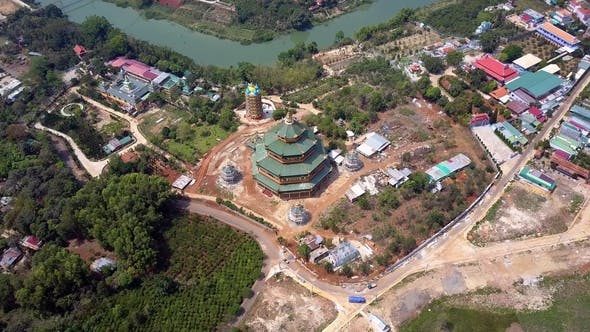 Flycam Rises Above Buddhist Temple and Boundless Landscape