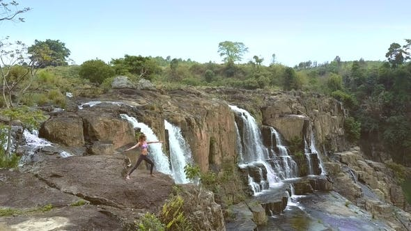 Pretty Girl Meditates in Yoga Pose By Pongour Waterfall