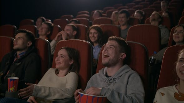 Thumbnail for Young People Laugh at Comedy Movie in Cinema Theatre. People Laughing at Cinema