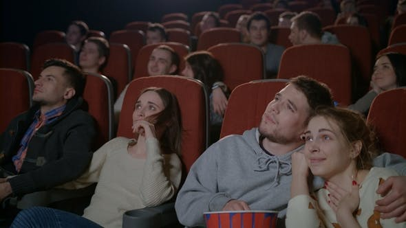 Love Couples Watching Movie in Cinema. Young Couple Embracing in Movie Theater