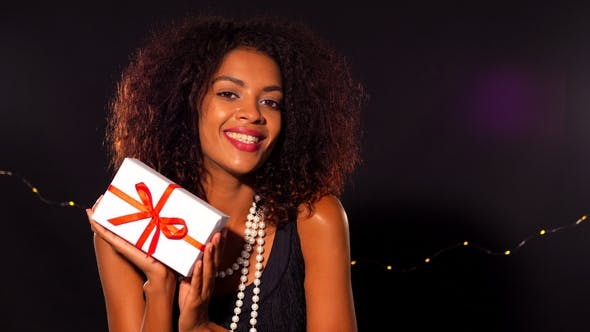 Thumbnail for African - American Young Woman in Party Kleid hält Geschenk-Box