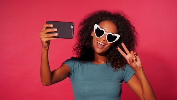 Cover Image for Smiling Happy African American Woman with Curly Hair in Green T-shirt Making Selfie on Smartphone