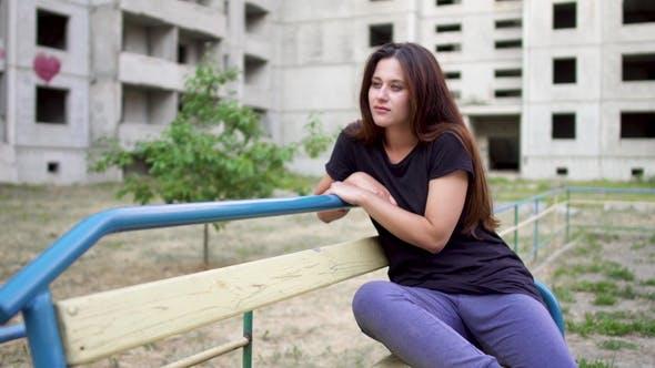 Thumbnail for Nervous Brunette Girl Is Sitting Near High Building