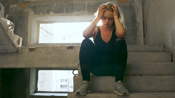 Thumbnail for Untidy Girl Is Sitting at the Stairs in an Abandoned Building