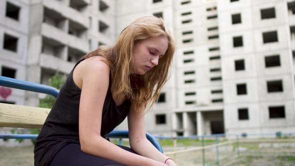 Thumbnail for Nervous Girl Is Sitting Near High Building