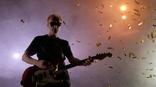 The Guitarist Performs on Stage. Stage Light, Smoke. From Above Fall Golden Confetti