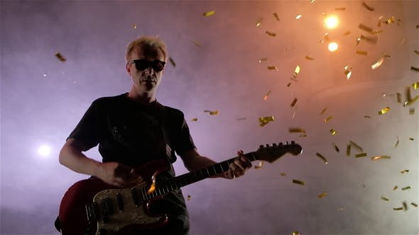 Thumbnail for The Guitarist Performs on Stage. Stage Light, Smoke. From Above Fall Golden Confetti