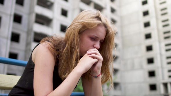 Cover Image for Nervous Girl Is Sitting Near High Building