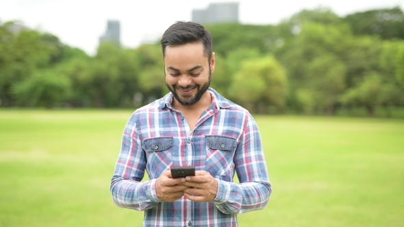 Thumbnail for Young Handsome Indian Man In Park Using Mobile Phone