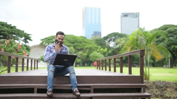 Thumbnail for Young Handsome Indian Man In Park Using Laptop Computer