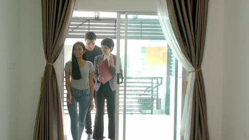 Professional Real Estate Agent Shows Modern House To a Young Couple
