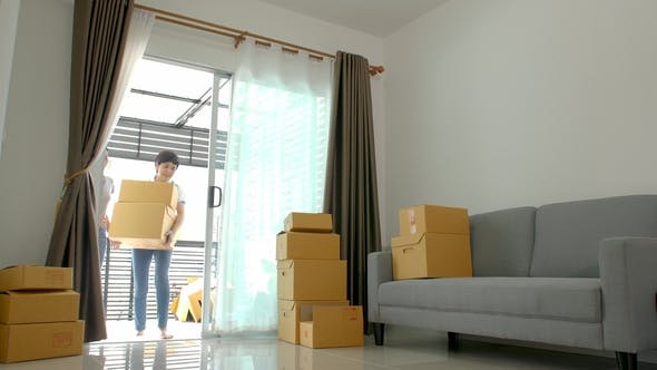 Cover Image for Happy Asian Women LGBT Lesbian Couple Holding Boxes Entering New Modern House