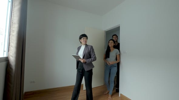 Cover Image for Professional Real Estate Agent Shows Modern House To a Young Couple.