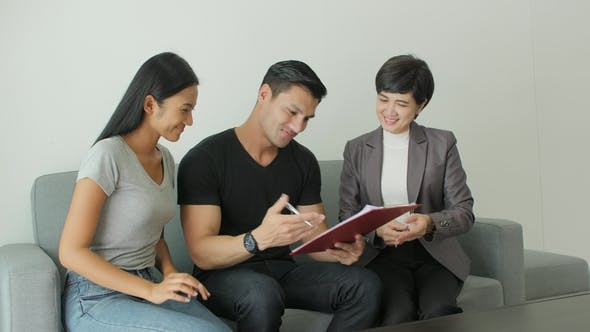 Cover Image for Young Attractive Couple Meeting Real-estate Agent, Signing Contract with Female Broker
